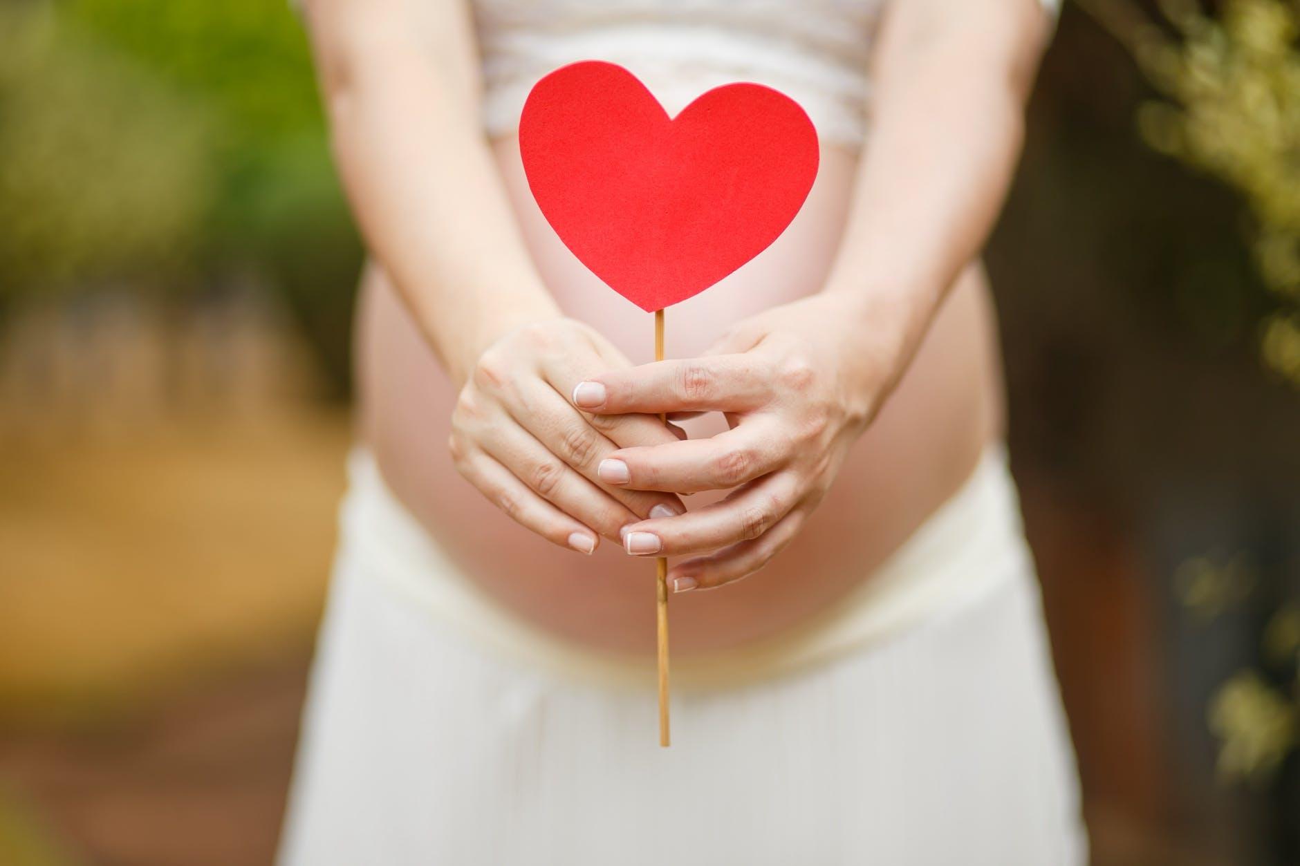 Eine Schwangere hält ein rotes Herz vor ihrem Bauch.