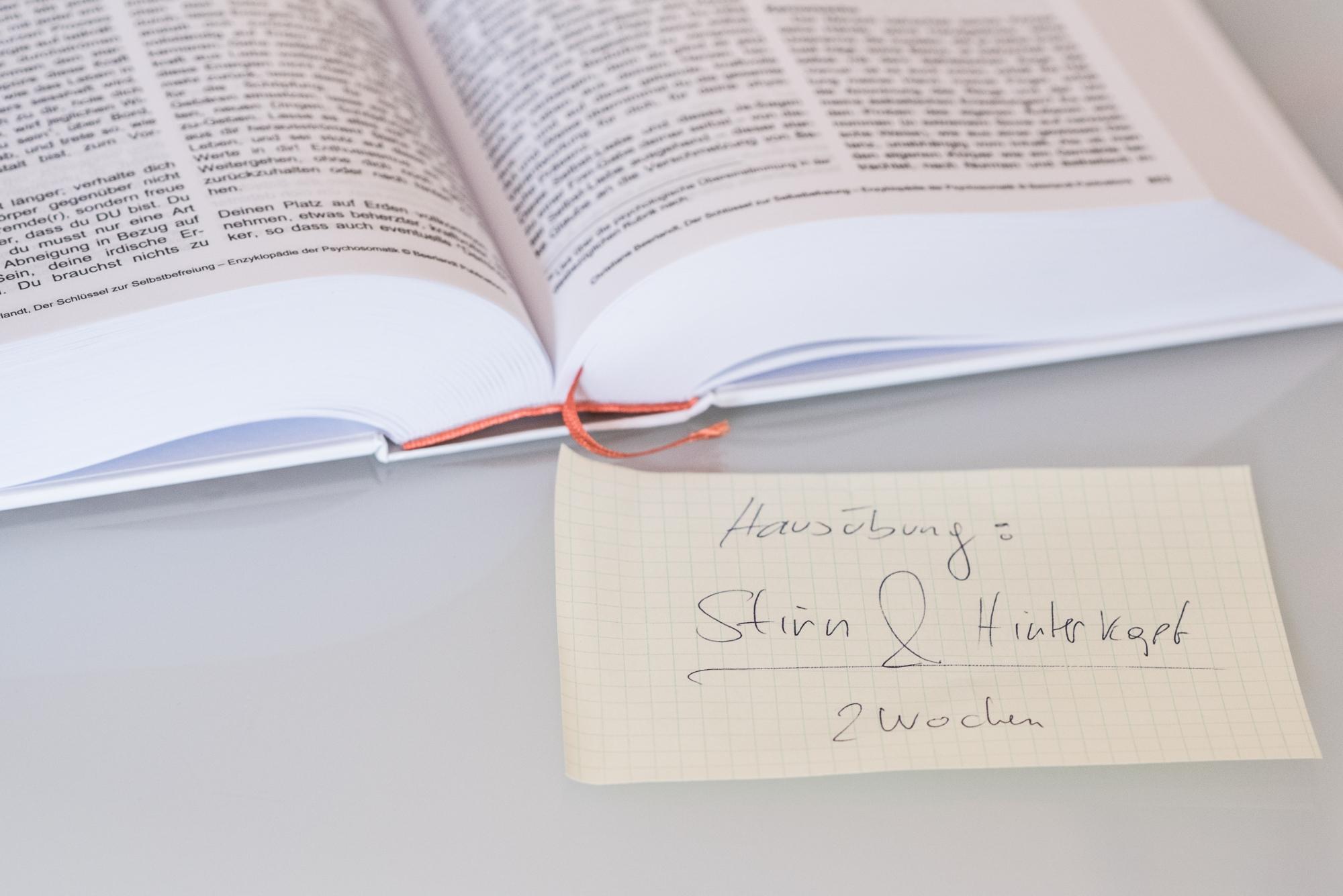Das Bild zeigt ein Buch und einen Zettel auf dem das Preis Leistungsverhältnis der Kinesiologie Praxis vermerkt ist.