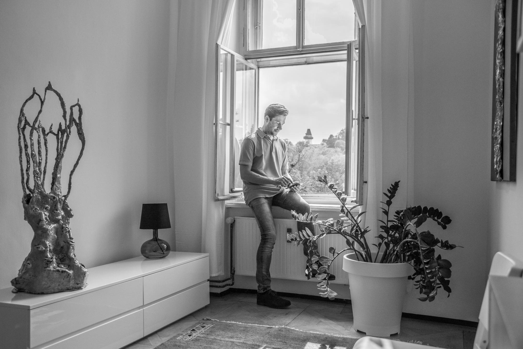 Aufnahme von Stefan Schwarz in seiner Praxis. Er hält sein Handy und tippt Kontaktdaten ein.